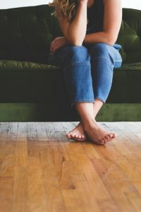 Barefoot woman is sitting on a velvet couch