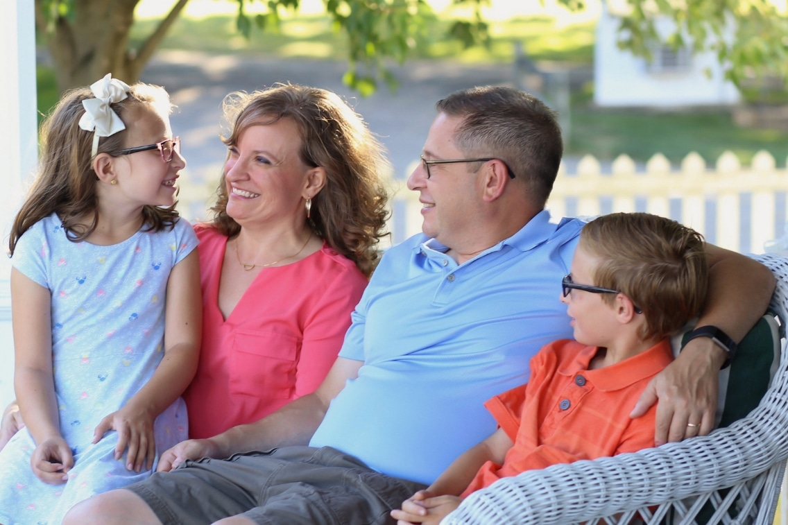 Daughter, mom, dad, and son sit together on a couch and laugh