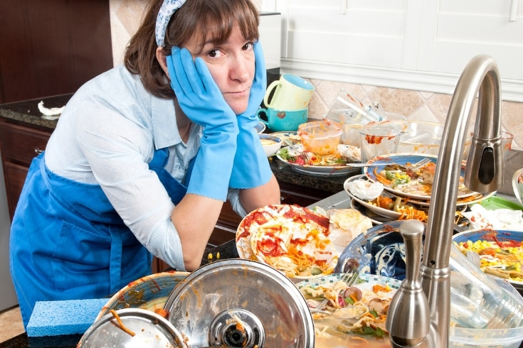 Overwhelmed woman stands by a counter filled with dirty dishes