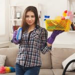 Woman stands in a clean living room, holding cleaning products