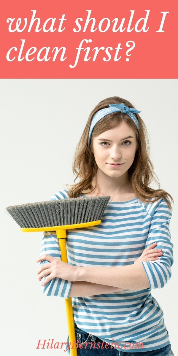 Woman stands with a broom, ready to clean