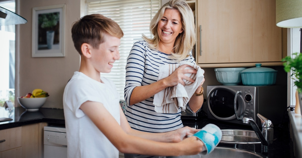 Mom and son handwash dishes together