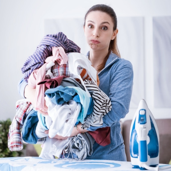 Woman holds pile of clean laundry.