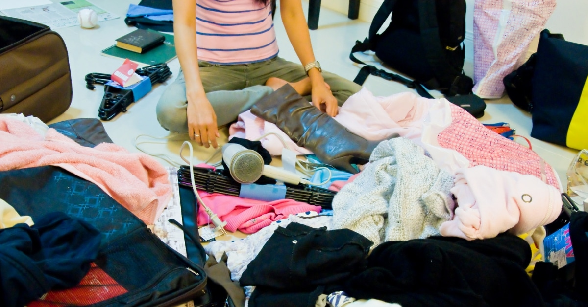 Woman sits surrounded by a cluttered mess
