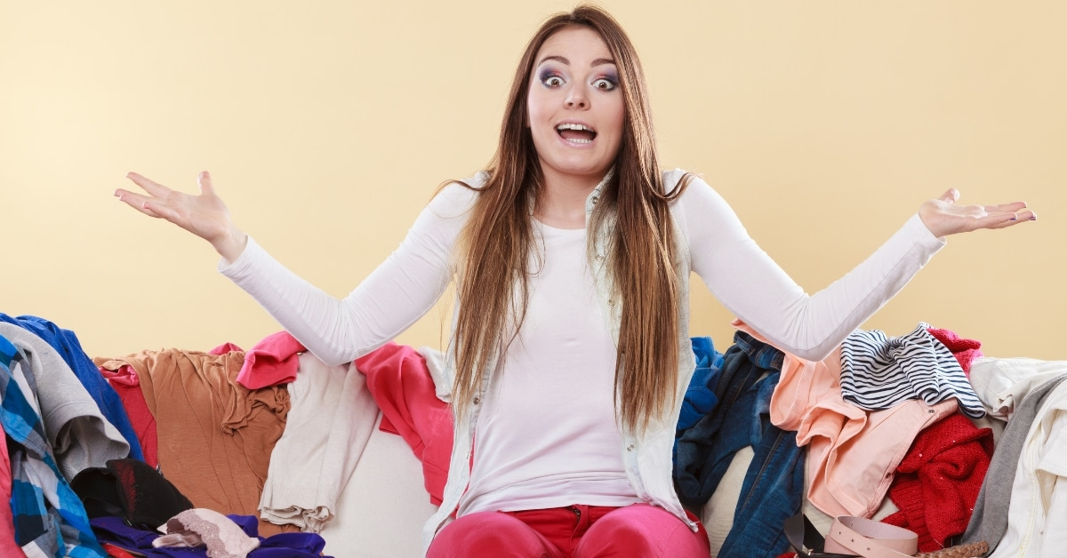 Woman is surrounded by clothes clutter