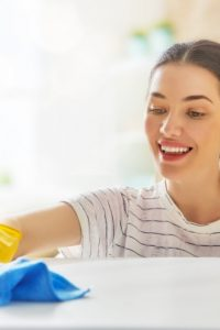Woman smiles as she cleans a countertop