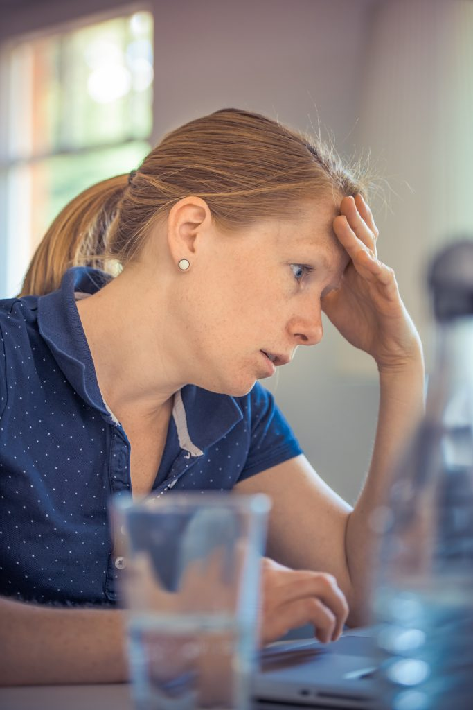 Woman sits at a table with a frustrated look on her face