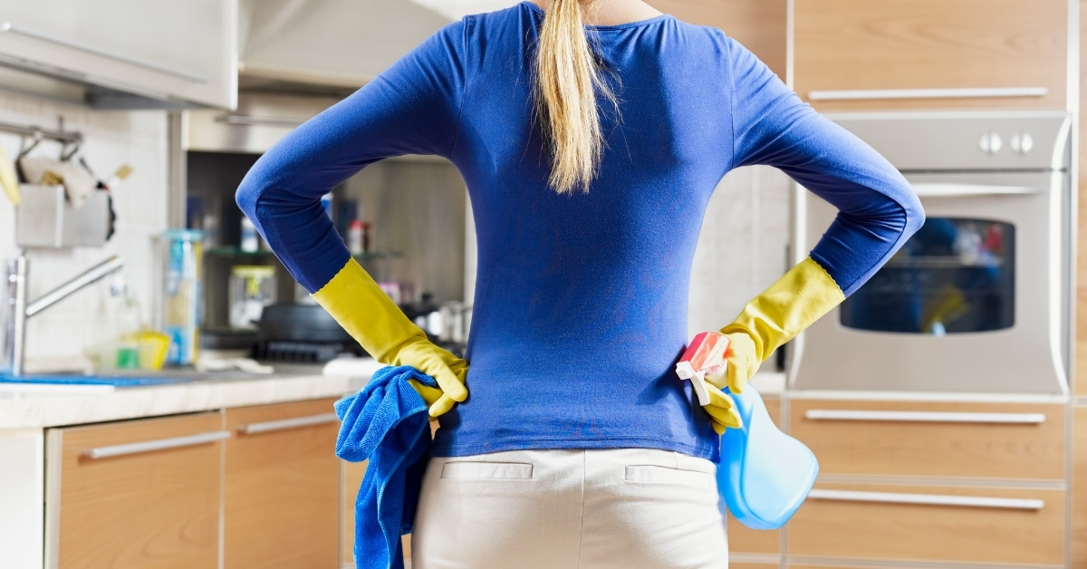 Woman stands in her kitchen, with her hands on her hips .... and cleaning supplies in her hands
