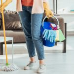 Woman holds a bucket of cleaning supplies