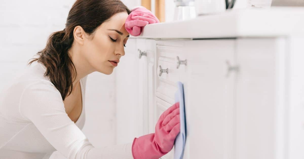 Woman wipes down cupboard door