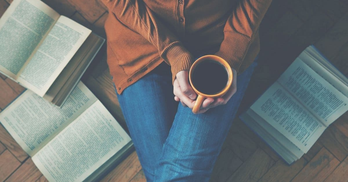 Woman sits on floor with coffee and books