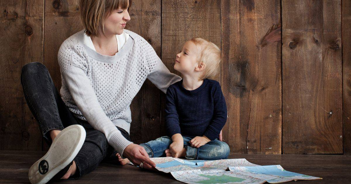 Mom and toddler son look at a map together