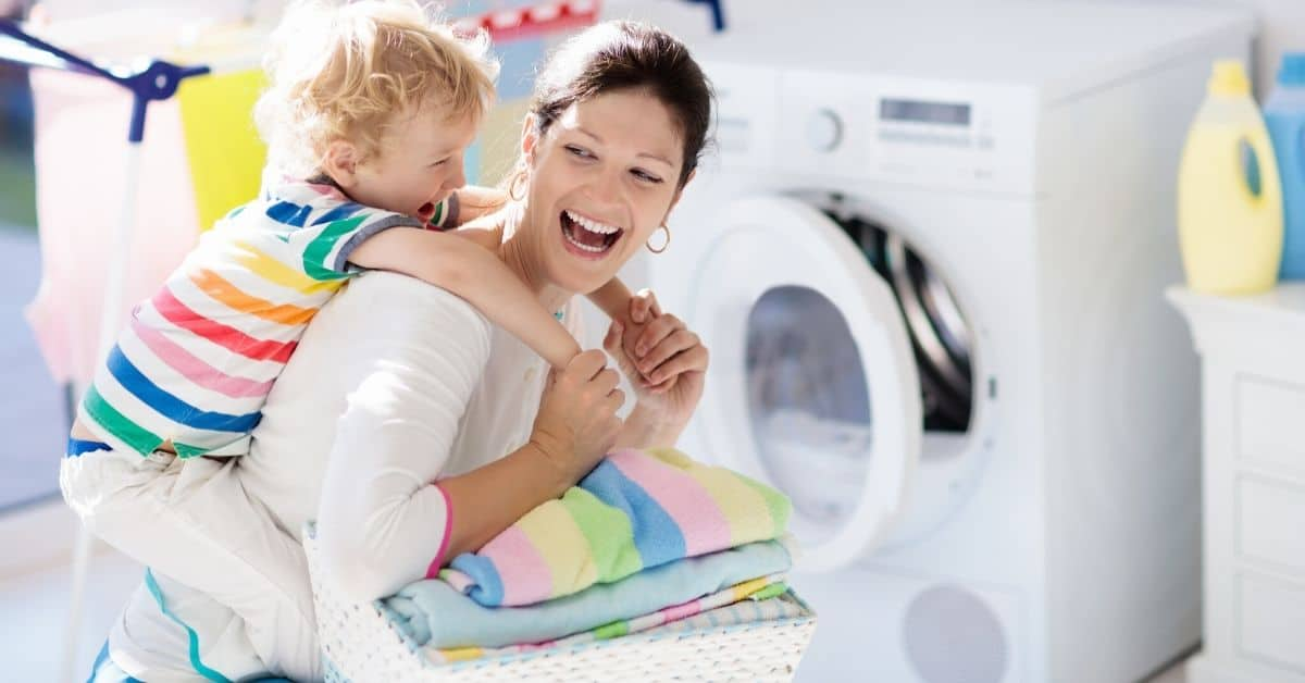 Mom and toddler fold clean laundry together