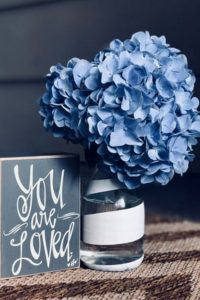 "Bouquet of hydrangeas and ""You Are Loved"" sign"
